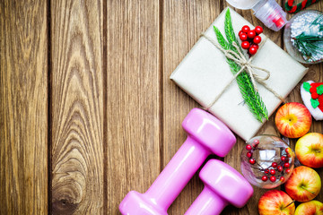 Fitness, healthy and active lifestyles Christmas gift concept, dumbbells, apples, gift box with Christmas ornaments decoration on wood background. Top view with copy space.