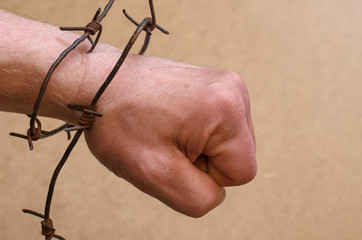 Strong man's hand clenched into a fist and tied with rusty barbed wire, freedom and struggle for independence themes, close-up, free space on the right, beige background
