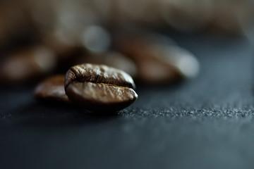 Foto op Canvas koffiebar Focus sur un seul grain de café sur un fond de nombreux grains de café sur un tableau noir de pierre