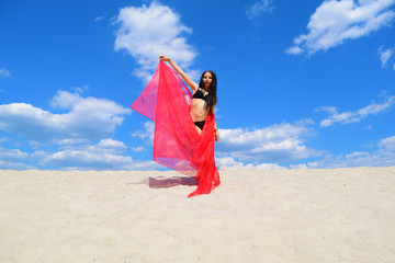 Naked brunette girl in a black swimsuit with a red towel on the sand. Hot summer.