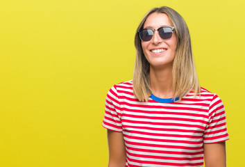 Young beautiful woman wearing sunglasses over isolated background looking away to side with smile on face, natural expression. Laughing confident.