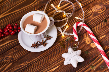 Beautiful composition with cup of cappuccino and Christmas cookies on the brown wooden table