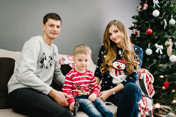 Happy family portrait, concept of a holiday. Mom, dad hugs son, sitting on the couch in home on the background of a Christmas tree. Happy New Year. Emotions of happiness. Close up.