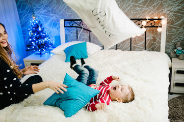 Christmas family! Happy mom, dad and little son in Santa Claus sweaters, play with pillows. Enjoy, love hugs, holidays people. Merry Christmas and Happy New year.