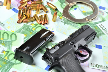 Pistol, loaded magazine, handcuffs and bullets on euro banknotes background