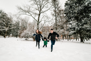 Happy family portrait walking, playing in a snow winter park, concept of a holiday. Mom, dad throws up son in nature. Close up. Emotions of happiness.