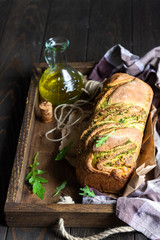 Homemade braided arugula pesto bread. Italian bread. Old wooden background. Copy space.