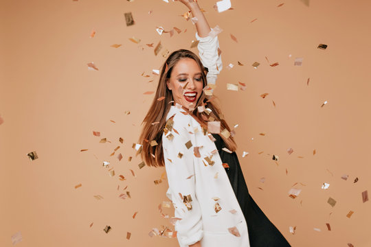 Indoor portrait of pretty young female model with light-brown hair wearing white jacket and black dress dancing and having fun on beige background with confetti
