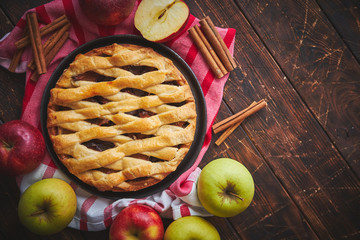 Homemade pastry apple pie with bakery products on dark rusty wooden kitchen table red and green apples and cinnamon. Traditional american dessert. Flat lay food background. Top view