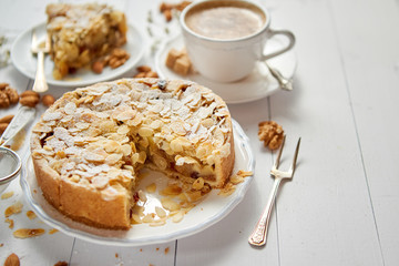 Horizontal shot of a whole round delicious apple cake tart with almond flakes served on wooden table. With coffee in a cup and slice of a pie on soucer.