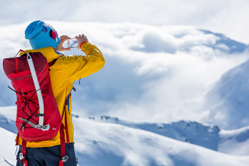 Fototapete - A skier is standing on the top. Sunny weather, clouds amd mountains.