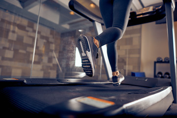 Close up of woman's legs running on treadmill. Gym interior.