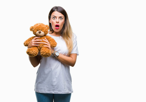 Young beautiful woman holding teddy bear plush over isolated background scared in shock with a surprise face, afraid and excited with fear expression