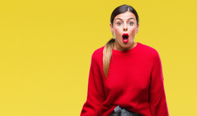 Young beautiful business woman wearing winter sweater over isolated background afraid and shocked with surprise expression, fear and excited face.