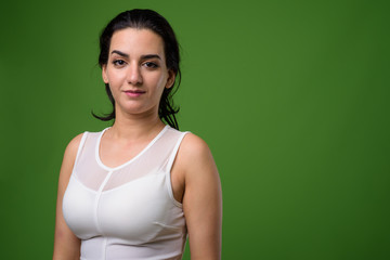 Portrait of beautiful Iranian woman against green background