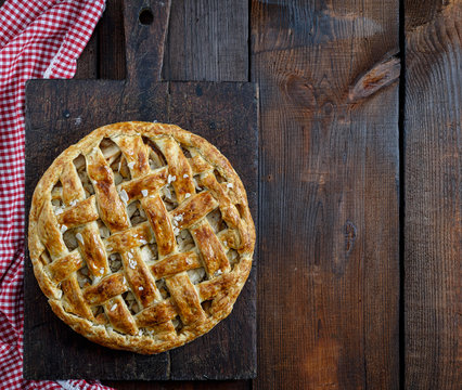 Baked whole round apple pie on a rectangular old brown board