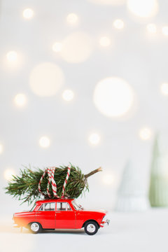 Red toy car with a christmas tree on the roof, garland bokeh on background, vertical orientation