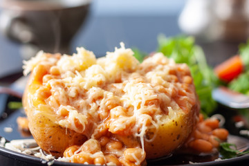 A baked potato topped with baked beans and cheese, served with a salad Wall mural