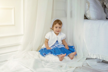 Funny and cute brunette little smiling girl playing and sitting relaxing in light white bedroom at home. White interior with big bed. Childhood, preschool, youth, relax concept