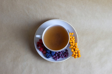 Cup of herbal tea with sea-buckthorn and other berries
