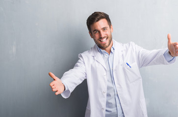 Handsome young professional man over grey grunge wall wearing white coat looking at the camera smiling with open arms for hug. Cheerful expression embracing happiness.