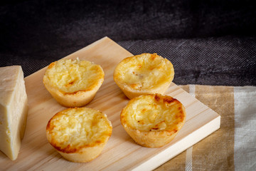 Homemade mini quiche with cheese on rustic background.