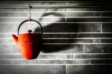 Red tea pot on kitchen wall