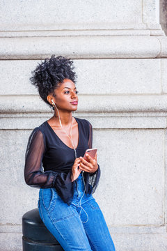 Young beautiful African American Woman with afro hairstyle wearing mesh sheer long sleeve shirt blouse, sitting on street in New York, listening music with earphone and cell phone, relaxing..