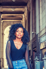 Young African American female college student with afro hairstyle, wearing mesh sheer long sleeve shirt blouse, blue jeans, walking on narrow old style street with high buildings on campus in New York