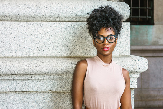 Portrait of Young African American Woman in New York. Young black female college student with afro hairstyle wearing sleeveless light color top, eye glasses, standing by column on street on campus..
