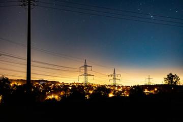 Dorf mit Hochspannungsleitungen bei Nacht mit Sternenhimmel