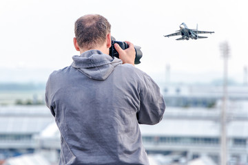 A photographer taking pictures at airport. Fighter aircrafts taking off.