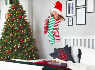 happy child  in pajamas with gifts jumping in bed on christmas morning