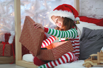happy child  in pajamas with christmas gifts