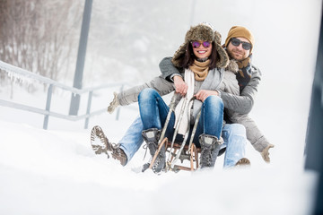 Photo sur Plexiglas Glisse hiver Young couple on sledge in winter outdoors