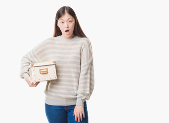 Young Chinese woman over isolated background holding a box scared in shock with a surprise face, afraid and excited with fear expression