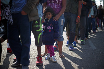 A migrant girl from Honduras queues for food outside of a temporary shelter in Tijuana