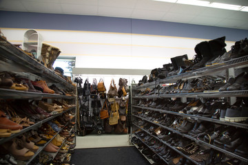 Isolated view of neutral colored womens pumps, shoes, sandals and purses on thrift store shelves and display - focus on purse display on back wall