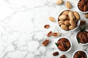 Flat lay composition with tasty pecan nuts on marble table. Space for text