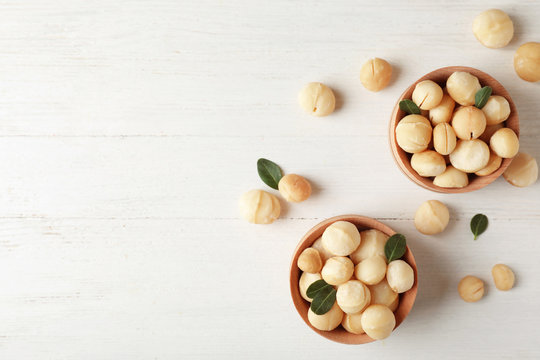 Bowls with shelled organic Macadamia nuts and space for text on white table, top view