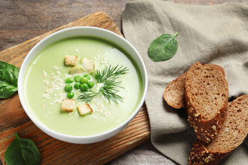 Fresh vegetable detox soup made of green peas served on table