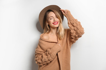 Beautiful young woman in warm sweater with hat on white background Wall mural