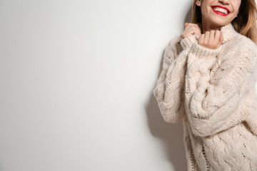 Beautiful young woman in warm sweater on white background. Space for text Wall mural