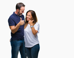 Middle age hispanic casual couple over isolated background doing happy thumbs up gesture with hand. Approving expression looking at the camera with showing success.