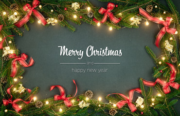 Merry Christmas and happy new year greetings in vertical top view dark blackboard with pine branches,ribbons and lights decorated frame.Xmas winter holiday season social media card background