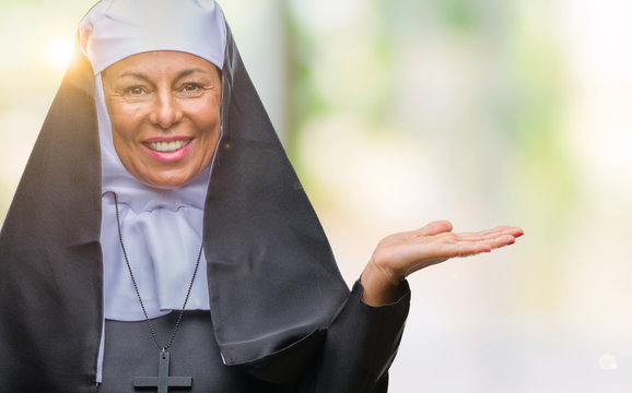 Middle age senior christian catholic nun woman over isolated background smiling cheerful presenting and pointing with palm of hand looking at the camera.