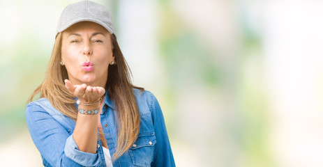 Beautiful middle age woman wearing sport cap over isolated background looking at the camera blowing a kiss with hand on air being lovely and sexy. Love expression.
