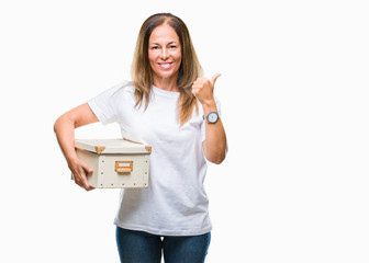 Middle age hispanic woman moving holding packing box over isolated background happy with big smile doing ok sign, thumb up with fingers, excellent sign