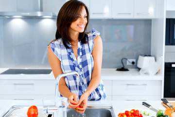 Beautiful woman standing in the kitchen and smiling