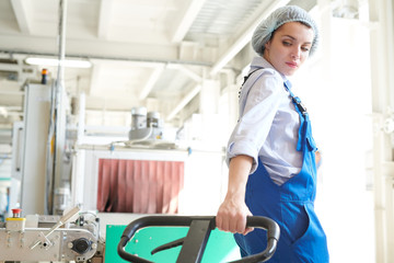 Back view portrait of young woman pulling moving cart in plant workshop, copy space